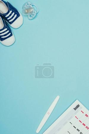top view of childish shoes, pacifier, calendar, pregnancy test isolated on blue