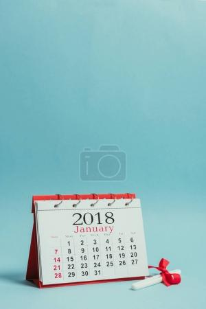close up view of calendar and pregnancy test with ribbon isolated on blue