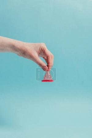 Photo pour Vue partielle de la femme tenant le préservatif ouvert à la main isolé sur bleu - image libre de droit