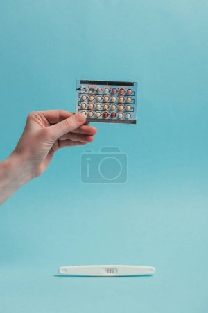 partial view of woman with contraceptive pills in hand and pregnancy test isolated on blue