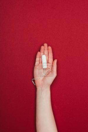 cropped shot of woman holding tampon in hand isolated on red