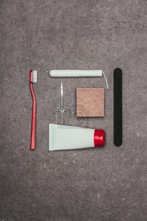 top view of arrangement of various feminine hygiene supplies on grey surface