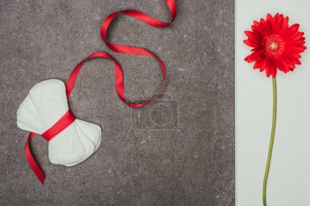 top view of arranged menstrual pads with ribbon and red flower on grey surface