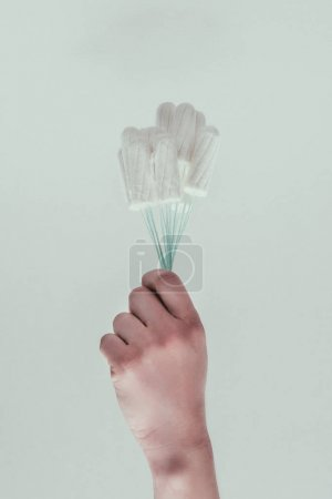 partial view of woman holding tampons in hand isolated on grey