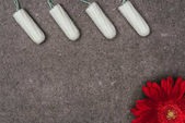 top view of arranged menstrual tampons and red flower on grey surface