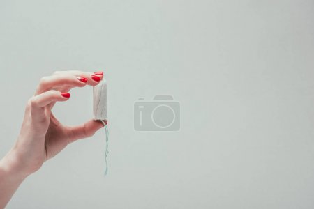 cropped shot of woman holding tampon in hand isolated on grey