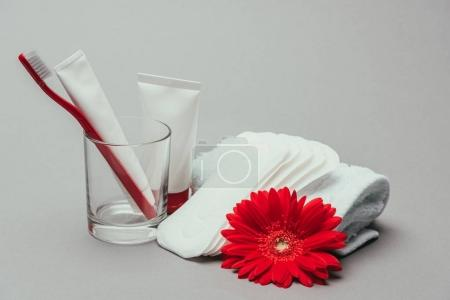 close up view of hygiene supplies, flower and towel isolated on grey