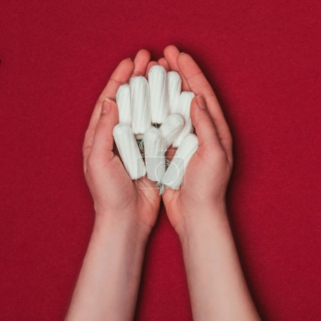partial view of woman holding tampons in hands isolated on red