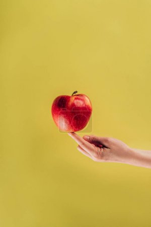 partial view of woman holding apple on finger
