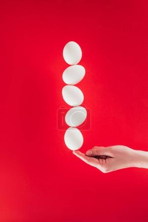 partial view of woman holding levitating raw chicken eggs on finger isolated on red
