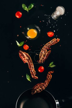 close up view of pieces of bacon, cherry tomatoes and raw egg yolk falling on frying pan isolated on black