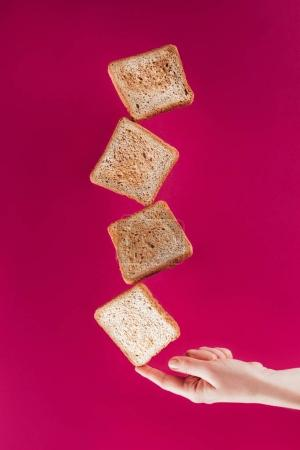 partial view of woman holding levitating toasts on finger isolated on pink