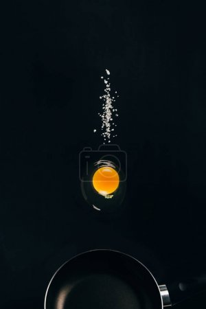 close up view of raw egg yolk and salt falling on frying pan isolated on black