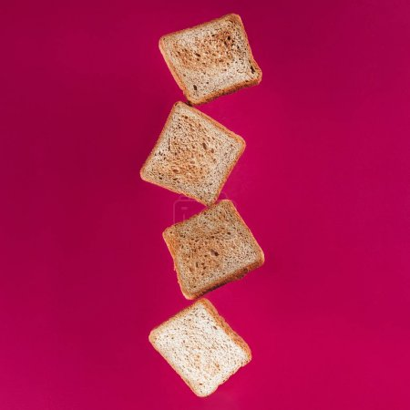 close up view of levitating toasts isolated on pink