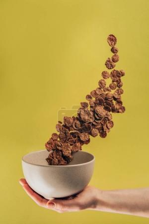 cropped shot of woman holding bowl with levitating chocolate corn flakes