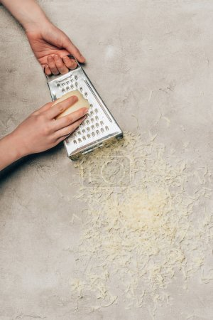 Close-up view of woman grating cheese on light background