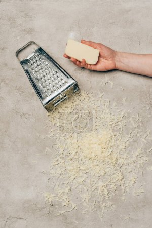 Close-up view of hand holding cheese by grater on light background