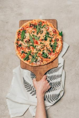 Photo for Close-up view of hand holding pizza on wooden cutting board on light background - Royalty Free Image
