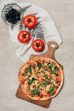 Delicious pizza on wooden cutting board and tomatoes on light background