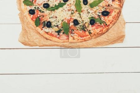 Italian pizza with olives on white wooden background