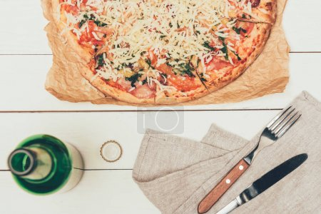 Italian pizza and opened bottle on white wooden background
