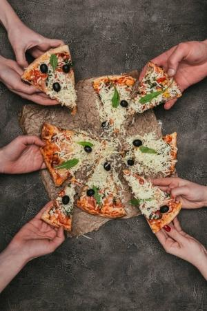 Close-up view of people taking slices of pizza on dark background