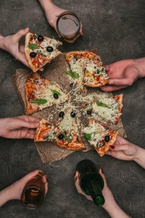 Close-up view of friends eating pizza on dark background