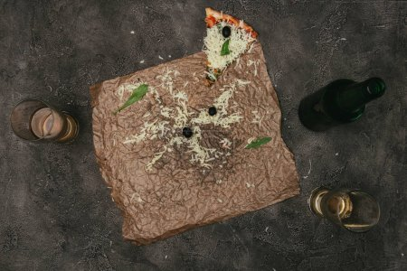 Pizza leftovers on craft paper with beer on dark background