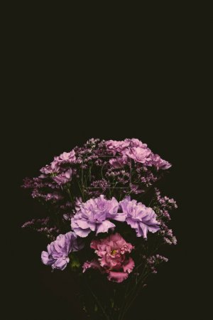 close-up view of beautiful floral bouquet of pink and purple blooming flowers isolated on black
