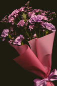 close-up view of beautiful floral bouquet of tender pink flowers with ribbon isolated on black