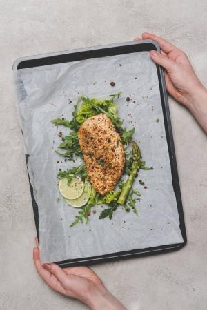 cropped shot of person holding tray with baking paper and healthy meat with arugula, lime and asparagus
