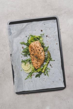 top view of healthy meat with arugula, lime and asparagus on baking paper