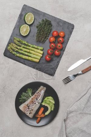 top view of gourmet fish with fresh healthy vegetables on grey
