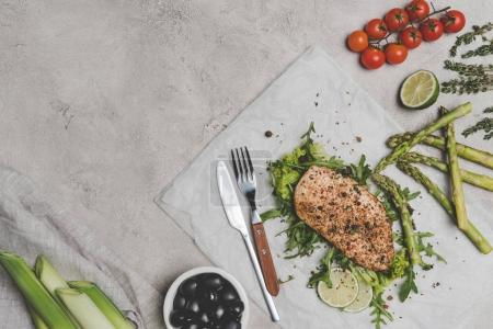 top view of delicious healthy baked meat with vegetables on grey