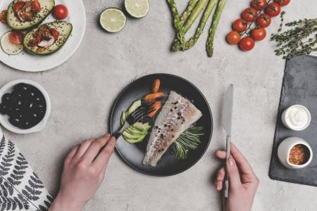 cropped shot of person eating fish with healthy vegetables on grey