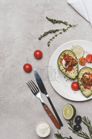 top view of gourmet healthy meal with avocado, lime and tomatoes on grey