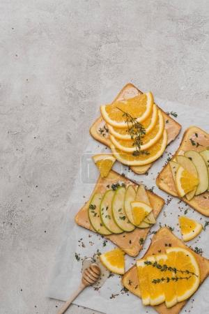 top view of healthy sandwiches with slices of apple and orange and honey dipper on grey