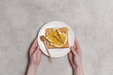 partial top view of person holding plate with fresh healthy sandwich with honey and orange slices on grey