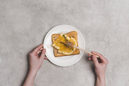top view of human hands with honey dipper and healthy sandwich with orange slices on grey