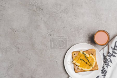 top view of tasty healthy toast with honey and orange slices and glass of juice on grey