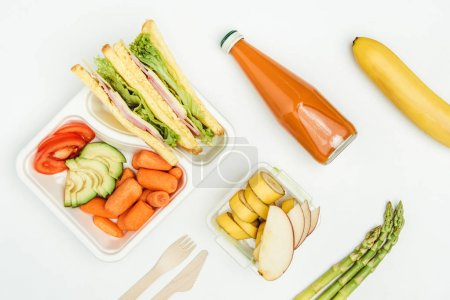 top view of sandwiches, fruits and vegetables in lunch boxes isolated on white