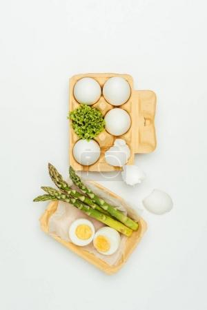 top view of eggs with tray and asparagus isolated on white