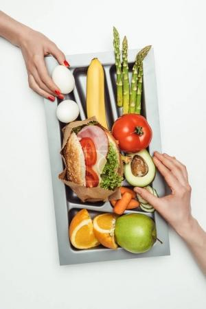 cropped image of women taking food from tray isolated on white