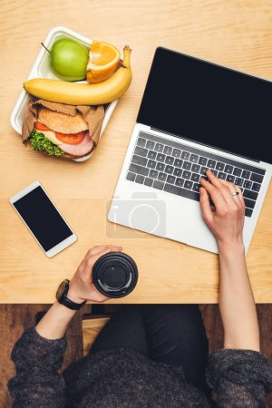 cropped image of woman holding disposable coffee cup and using laptop