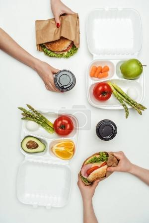 cropped image of women eating take away burgers and drinking coffee to go isolated on white