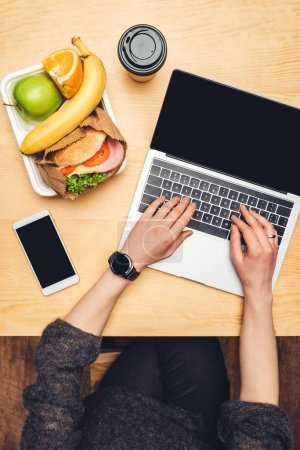cropped image of woman using laptop at table with food on container
