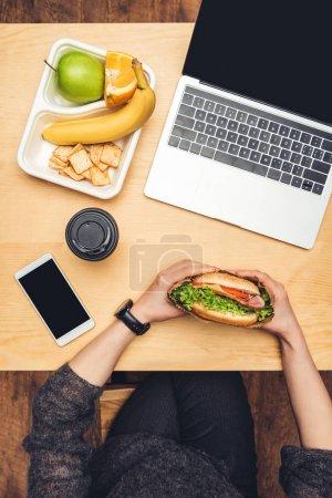 Photo pour Cropped image de femme manger le hamburger à table avec fruits et gadgets - image libre de droit