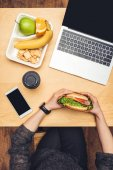 cropped image of woman eating burger at table with fruits and gadgets