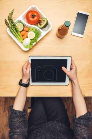 cropped image of woman sitting at table with food in container and using tablet