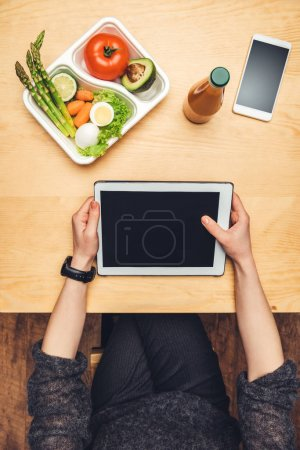 Photo for Cropped image of woman sitting at table with food in container and using tablet - Royalty Free Image